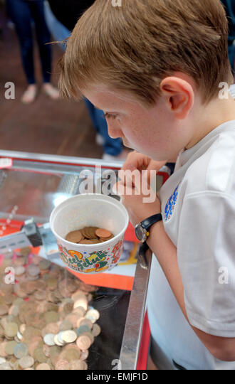 A boy playing putting Two pence coins in a tipping point machine in a seaside arcade - Stock Image
