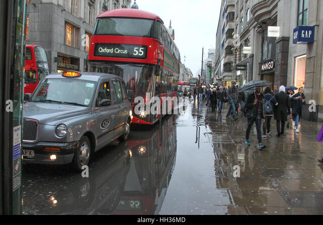 Pedestrians and traffic on Oxford Street seen by a large puddle of rain water following a rain shower on January - Stock Image