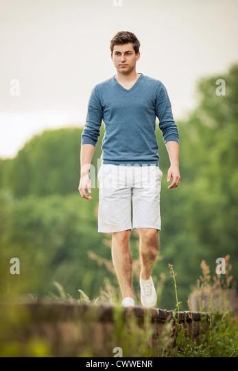 Man walking on train tracks - Stock Image
