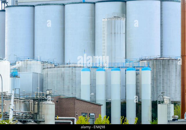 Gigantic silos on an industrial site. All are grey and some have blue tops. Almost form a solid background of metal. - Stock Image