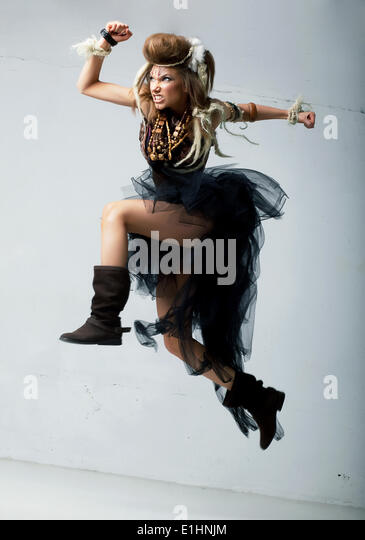 Tribe. Wild tribal person jumping - retro fashion ancient style. Antique - Stock Image