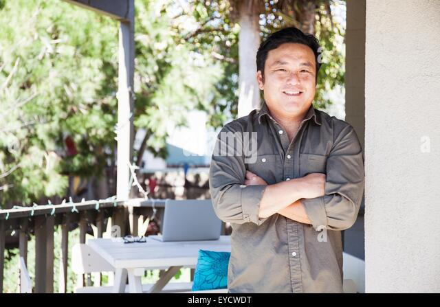 Portrait of mature man with arms folded on porch - Stock Image