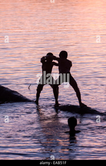 Cambodia.  Angkor Thom.  Boys Wrestling on Edge of Lake. - Stock Image