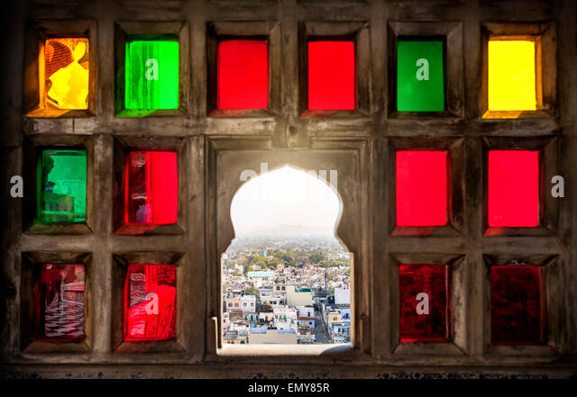 Town view from the colorful mosaic window in City Palace museum of Udaipur, Rajasthan, India - Stock-Bilder