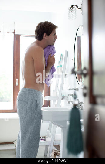 Man in bathrom drying face with towel - Stock-Bilder