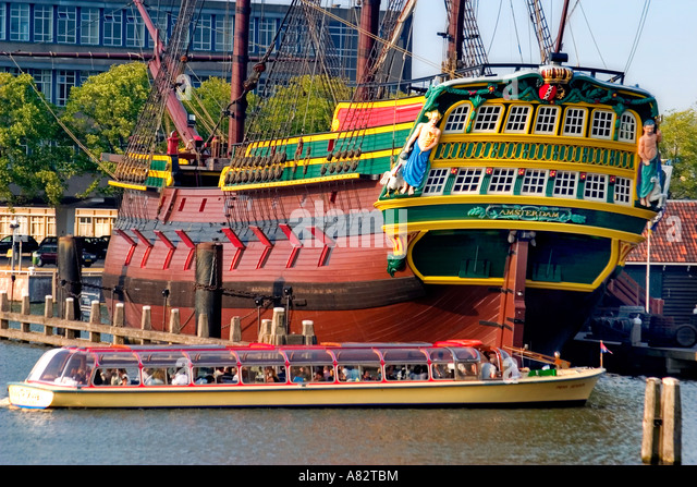 Amsterdam canal boat tour at historic harbour museumship Amsterdam replica of east india Company ship 17th century - Stock Image