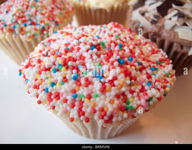 A cup cake covered in hundreds and thousands - Stock Image