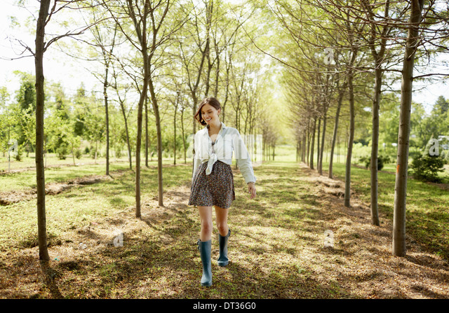 A young woman walking down an avenue of trees in woodland - Stock Image