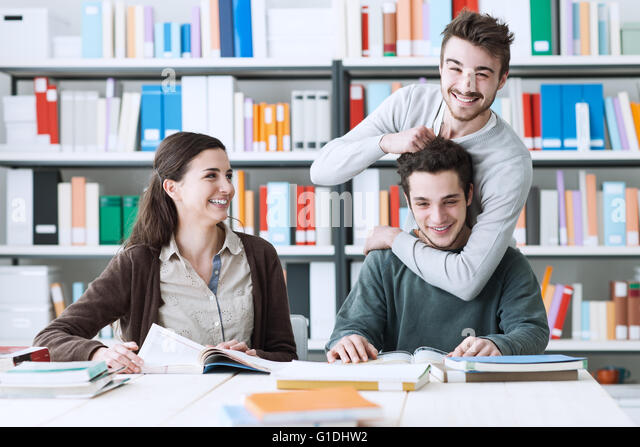 Playful schoolmates studying together at the library, togetherness and friendship concept - Stock Image