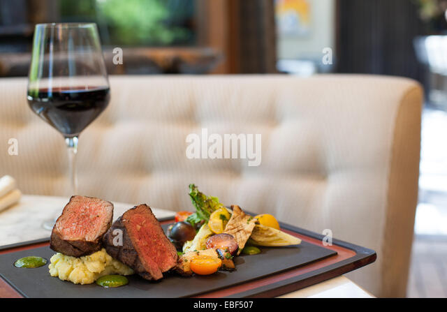 Beef entree with red wine on table in high end restaurant - Stock Image