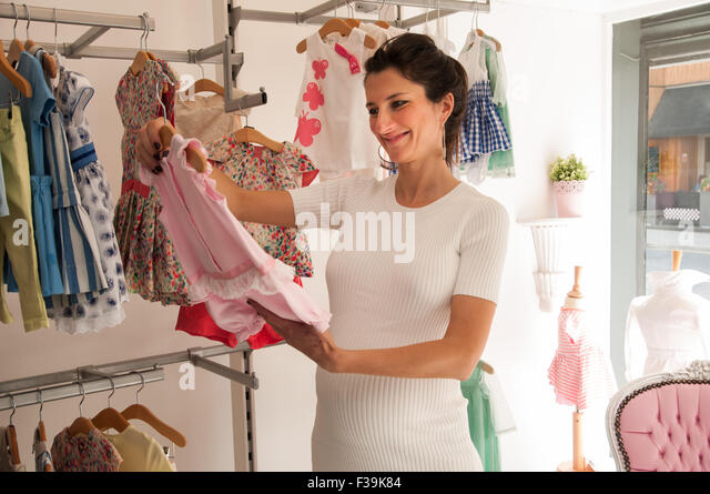 Portrait of a smiling  Pregnant woman in a shop looking at baby clothing - Stock Image