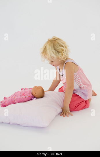 Girl playing with a doll - Stock Image