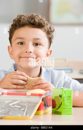 Schoolboy with packed lunch - Stock Image