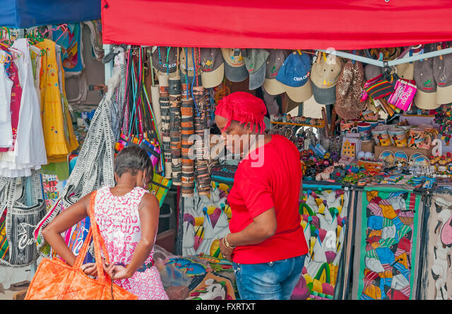 Young girl tries on clothes at outdoor gift store, Willemstad Curacao - Stock Image