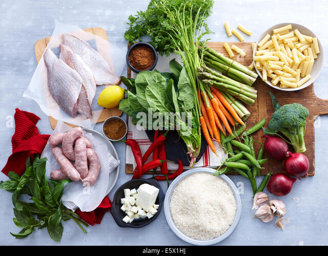 Overhead view of fish, pork sausage, feta and selection of fresh organic herbs and vegetable - Stock-Bilder