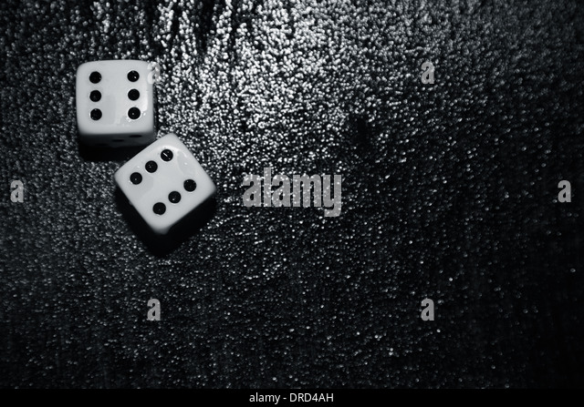 Gambling dices on a wet surface - Stock Image