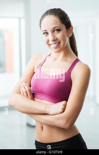 Young smiling woman posing at the gym and looking at camera, fitness and healthy lifestyle concept - Stock Image
