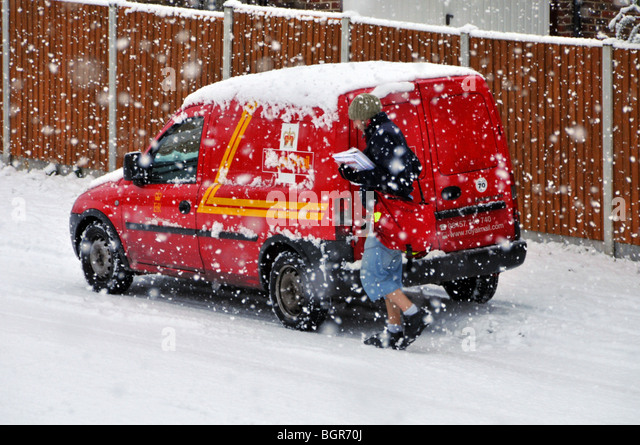 Royal Mail delivery van and postman walking residential street during snow storm (number plate obscured) - Stock Image