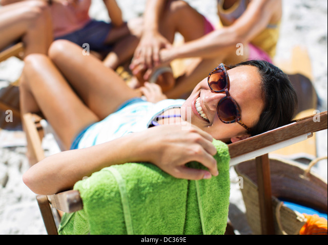 Portrait of happy woman sitting in lounge chair on beach - Stock Image