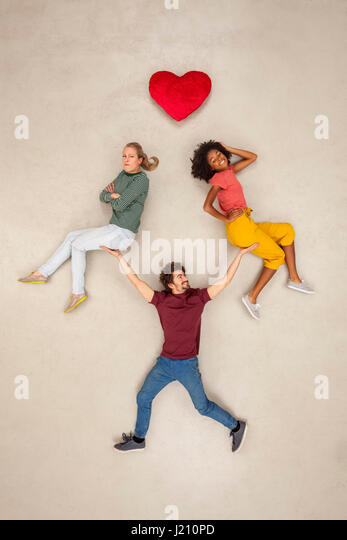 Man balancing two women on his hands, not making a decision - Stock Image