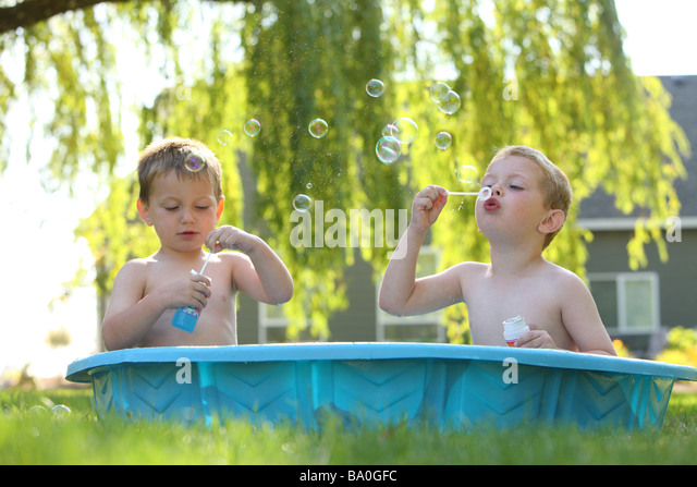 Two young boys in pool blowing bubbles - Stock Image