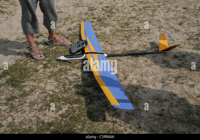 Radio-controlled glider (glider model) on the floor with the remote. - Stock Image