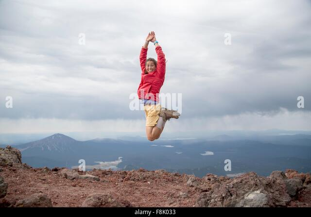 Young woman jumping for joy at the summit of South Sister volcano, Bend, Oregon, USA - Stock Image