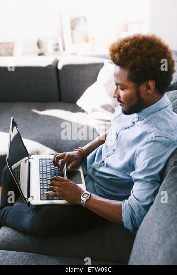 Young Afro American man sitting on couch, using laptop - Stock-Bilder