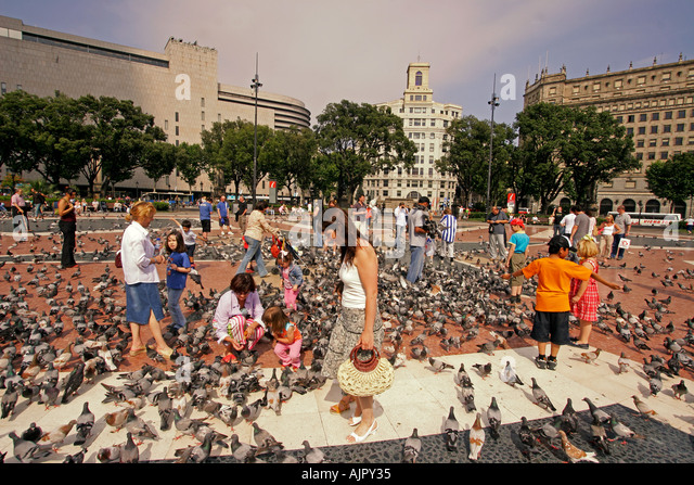 ESP Spanien Barcelona Plaza de Catalunya tourists feeding pigeons - Stock Image