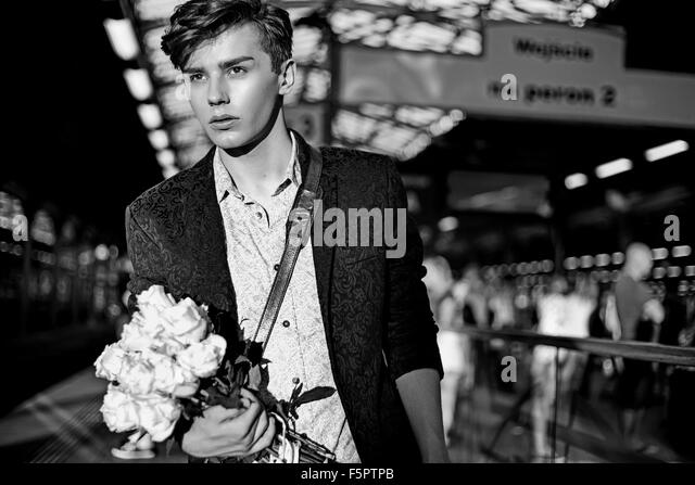 Charming guy standing in the railway station - Stock Image