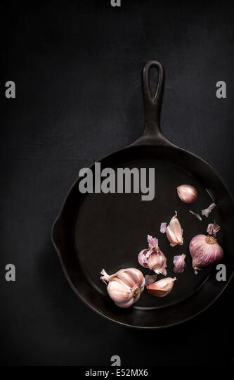 Purple garlic cloves in a cast iron skillet. Dark moody setting. - Stock Image