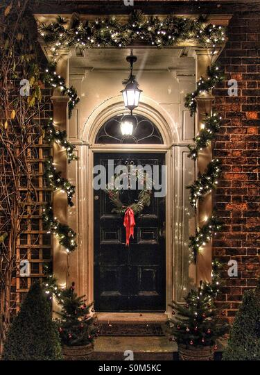 A traditional doorway decorated for Christmas with a wreath and lights. - Stock Image