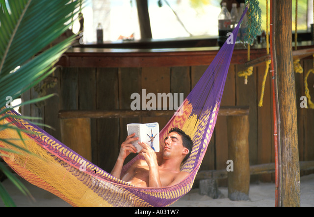 Mexico man in hammock reading yucatan playa del carmen cancun area - Stock Image
