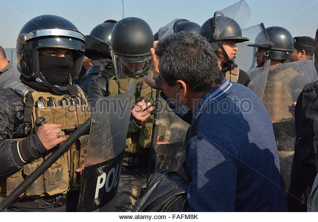 Baghdad, Iraq. December 29th, 2015. IRAQ, Baghdad: A police line blocks a protester during a demonstration on December - Stock Image