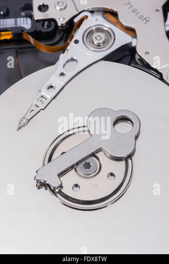 Generic key on hard disk drive platter - as visual metaphor for data encryption, data security, file access, access - Stock Image