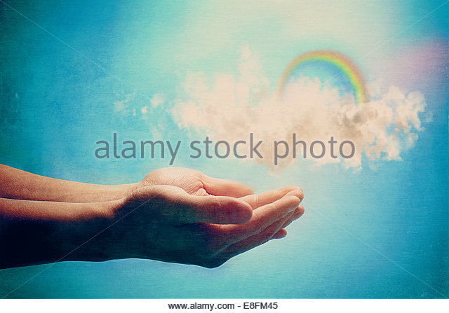 Human hands holding rainbow and clouds - Stock Image