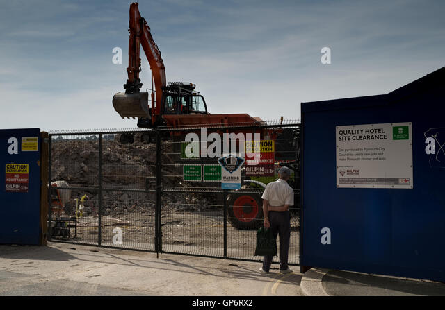 A man looks on as clearing works take place on the site of the old Quality Hotel recently demolished in Plymouth - Stock Image