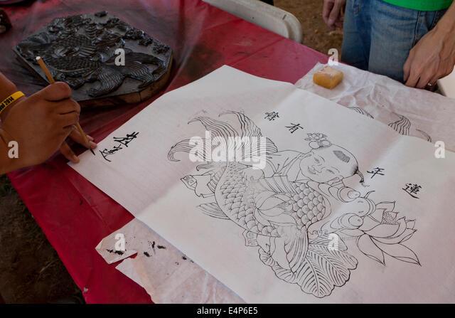 Man signing Chinese woodblock print - Stock Image