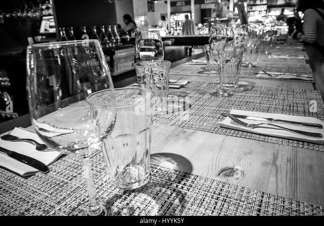 Empty glasses are set up on a bar in a restaurant, people in the background. - Stock Image