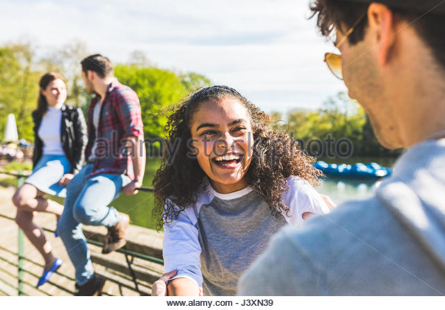 Young couple laughing on lakeside in Battersea Park - Stock Image