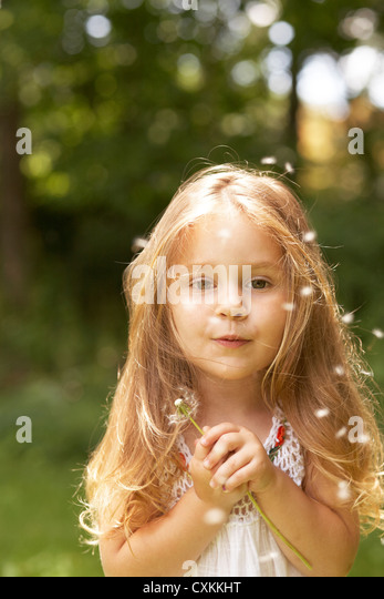 Little girl wishing on a dandelion - Stock Image