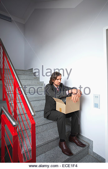 Young man sitting steps jobless depressed alone - Stock Image