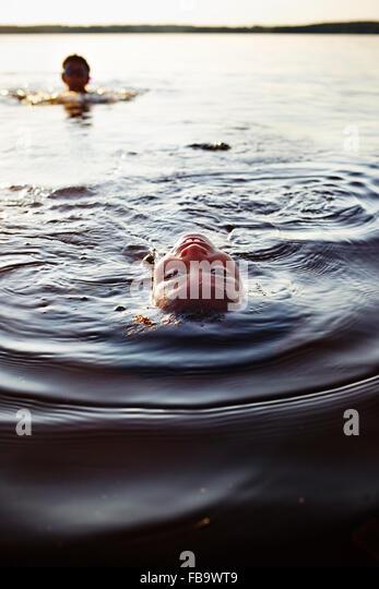 Sweden, Vastra Gotaland, Skagern, Children (6-7, 10-11) swimming in lake - Stock Image