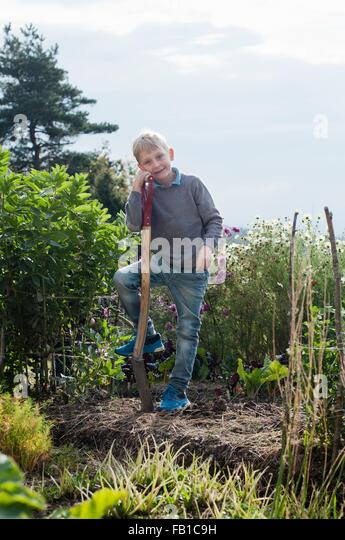 Portrait of boy digging in organic garden - Stock Image