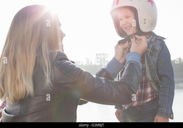 Young woman putting crash helmet on daughter, smiling - Stock Image