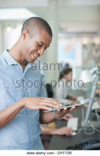 Man using digital tablet in office - Stock Image