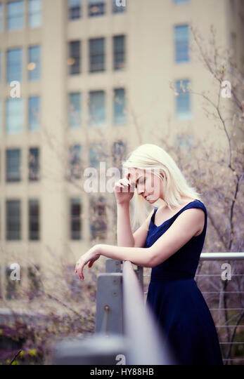 Young women looking out from a balcony in New York - Stock Image