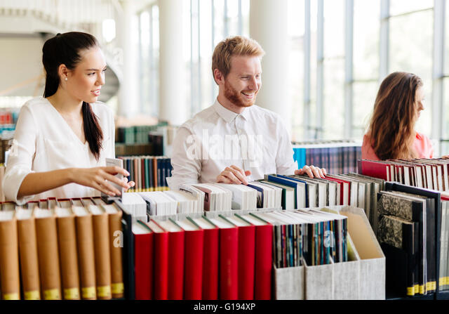 Group of students studying in library and reading books - Stock Image
