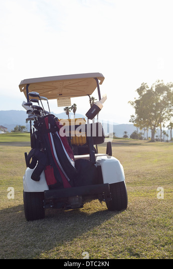 Parked golf buggy on green - Stock Image