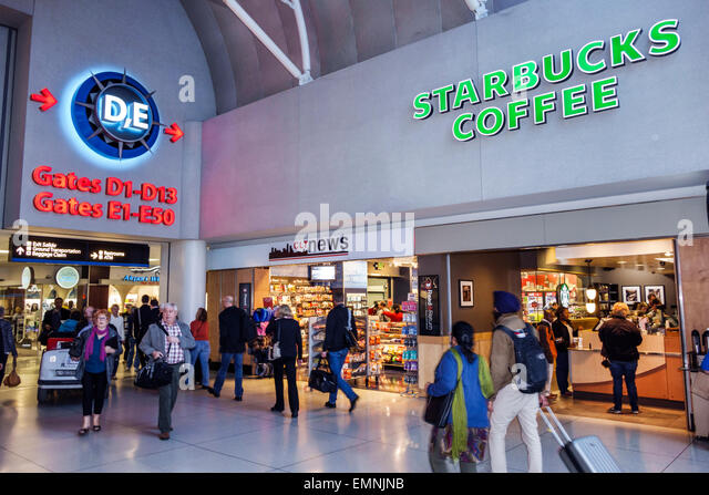 North Carolina Charlotte Charlotte Douglas International Airport CLT terminal concourse gate area Starbucks Coffee - Stock Image